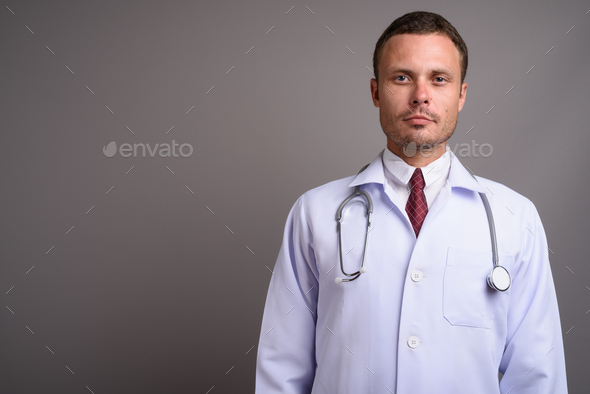 Portrait of handsome man doctor against gray background - Stock Photo - Images