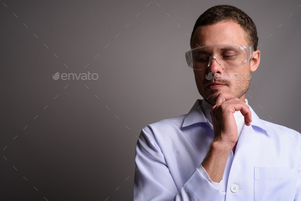 Handsome man doctor wearing protective glasses against gray back - Stock Photo - Images