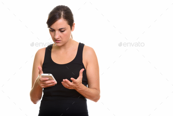 Studio shot of angry woman holding mobile phone - Stock Photo - Images
