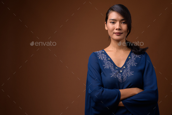 Studio shot of beautiful Asian woman against brown background - Stock Photo - Images