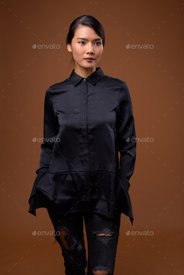 Studio shot of beautiful Asian businesswoman with hair tied - Stock Photo - Images