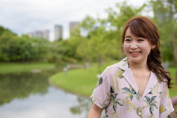 Young beautiful Asian tourist woman relaxing at the park - Stock Photo - Images