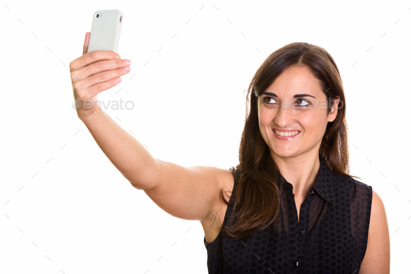 Studio shot of happy beautiful woman smiling while taking selfie - Stock Photo - Images