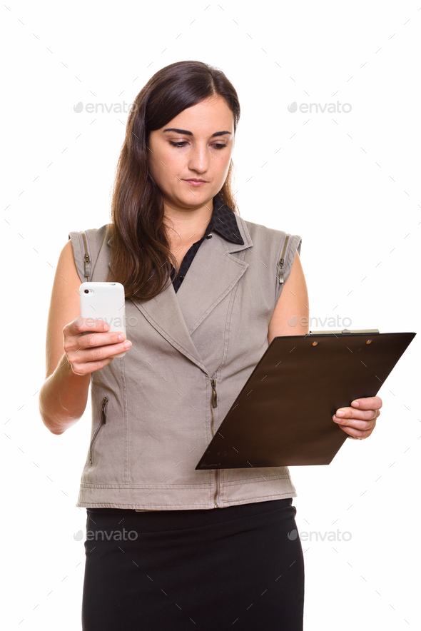 Portrait of young beautiful businesswoman using phone while holding clipboard - Stock Photo - Images