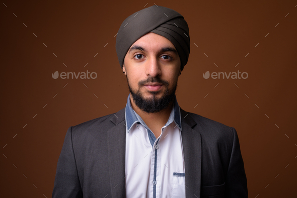 Young bearded Indian Sikh businessman wearing turban - Stock Photo - Images