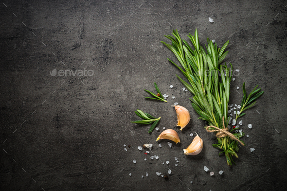 Rosemary sprig on a black kitchen table - Stock Photo - Images