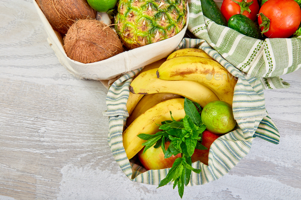 Flat lay of eco friendly grocery shopping cotton bags with organic fruits and vegetable - Stock Photo - Images