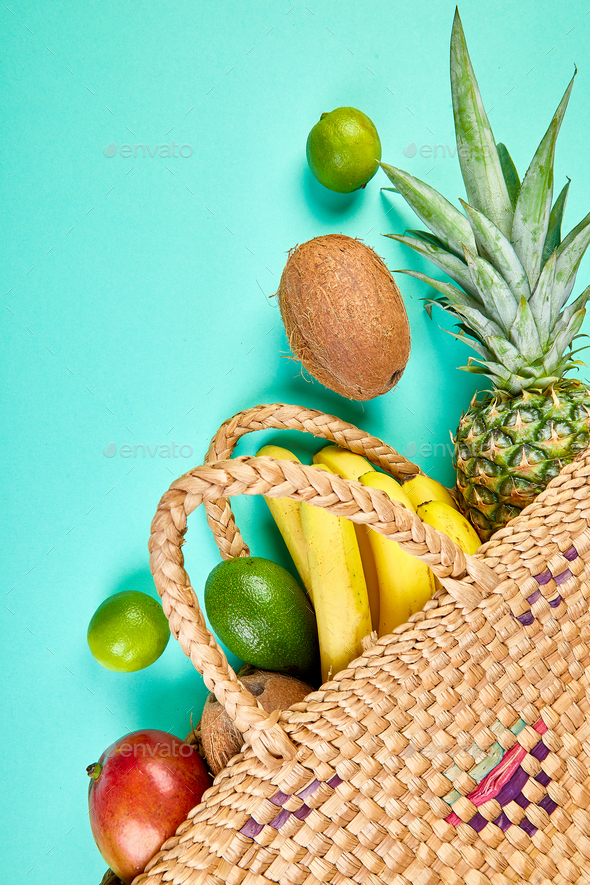 Grocery shopping bamboo bag  with organic exotic fruits on blue background. - Stock Photo - Images