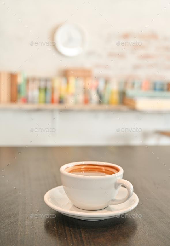 White coffee mug on wooden table, background, bookshelf. - Stock Photo - Images