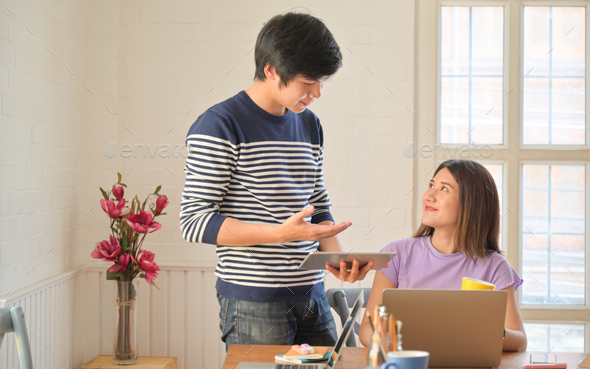 Male and female students are consulting projects for teacher presentations with tablets and laptops. - Stock Photo - Images
