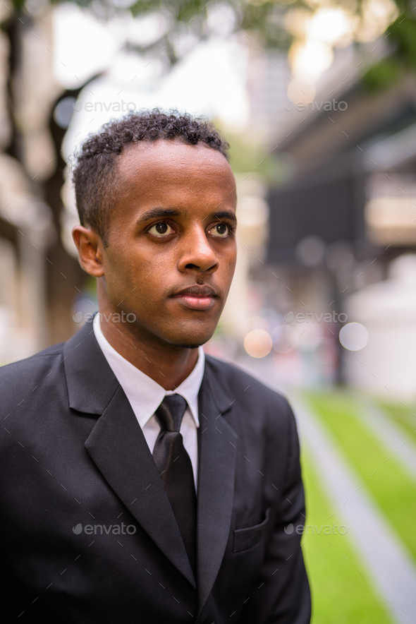 Face of young African businessman thinking outdoors in city - Stock Photo - Images