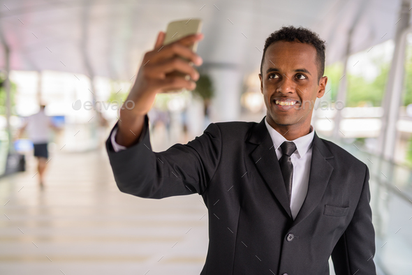 Happy African businessman taking selfie using mobile phone outdoors - Stock Photo - Images