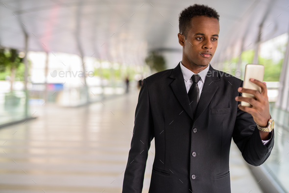 Portrait of successful young African businessman using mobile phone outdoors - Stock Photo - Images