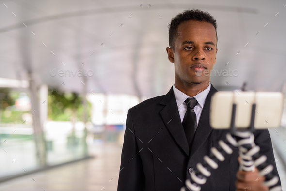 Young African businessman using mobile phone and vlogging outdoors in city - Stock Photo - Images
