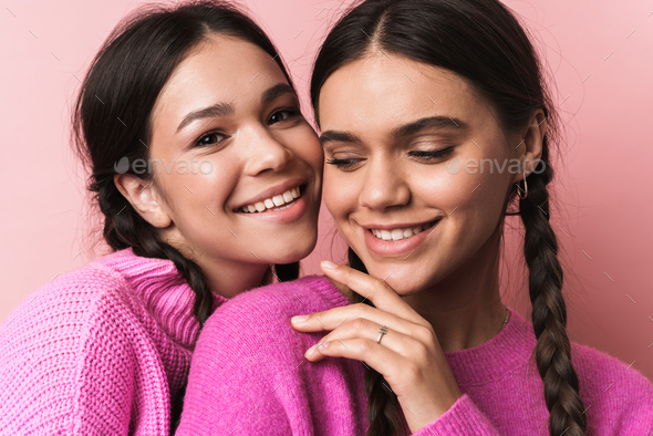 Image of two happy girls with braids in casual clothes smiling at camera - Stock Photo - Images