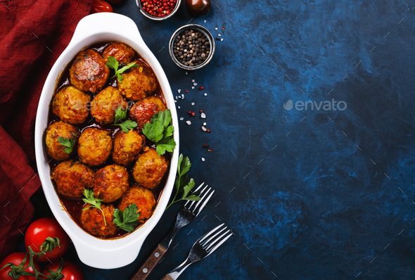 Meatballs with tomato sauce and spices in baking dish on blue kitchen table - Stock Photo - Images