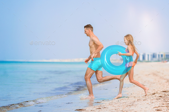 Little girl and happy dad having fun during beach vacation - Stock Photo - Images