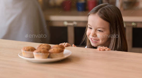 Kids and sweets concept. Adorable little girl craving cookies, looking at sweets in kitchen - Stock Photo - Images