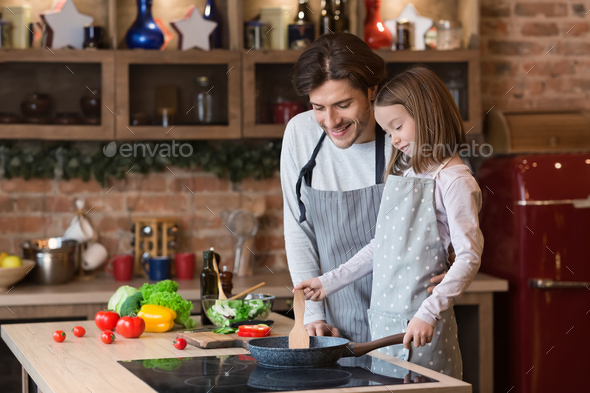 Dad teaching his cute daughter how to cook food on pan - Stock Photo - Images