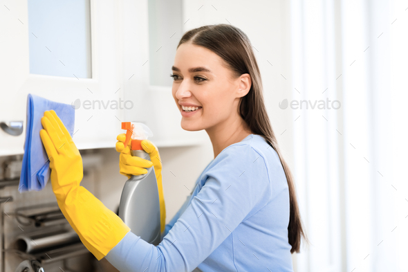 Young woman cleaning kitchen furniture using spray - Stock Photo - Images