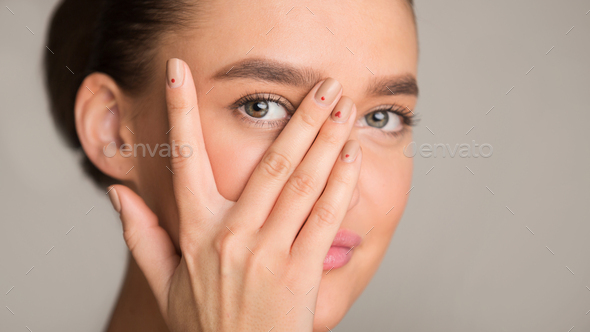 Young woman looking at camera through fingers - Stock Photo - Images