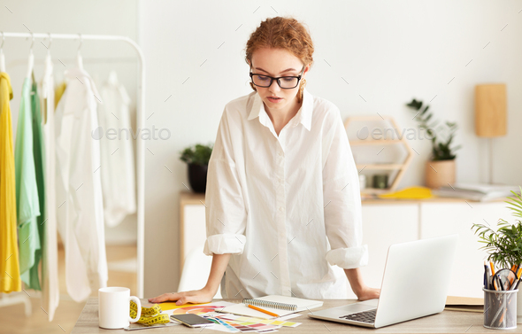 Serious fashion stylist working and standing at desk - Stock Photo - Images