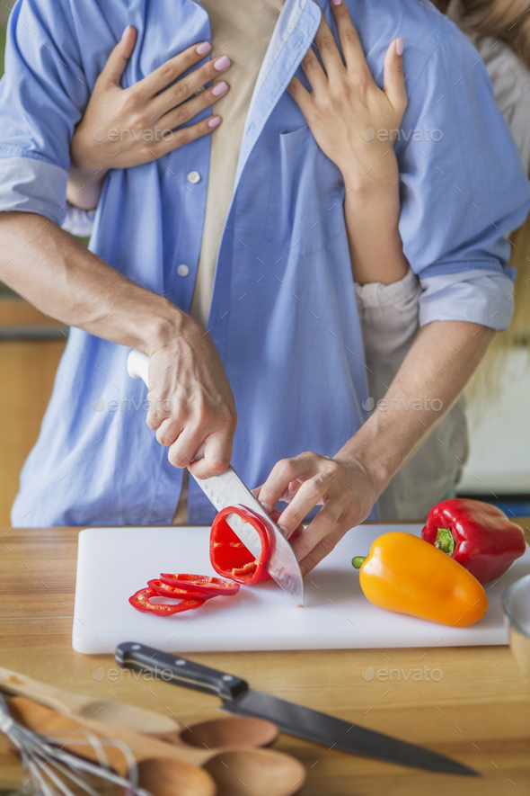 Happy romantic young couple cutting fresh paprika - Stock Photo - Images