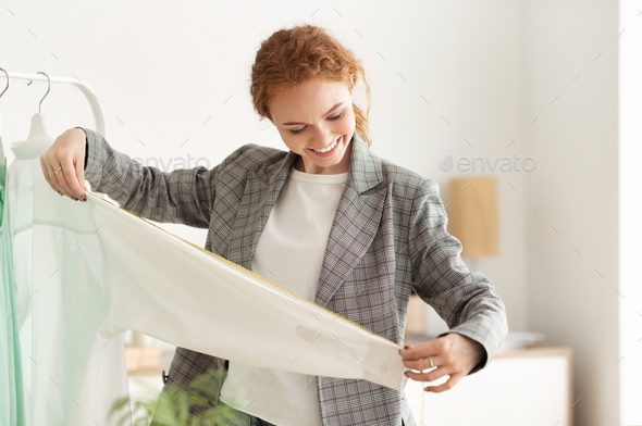 Dressmaker Measuring New Clothing Collection In Showroom - Stock Photo - Images