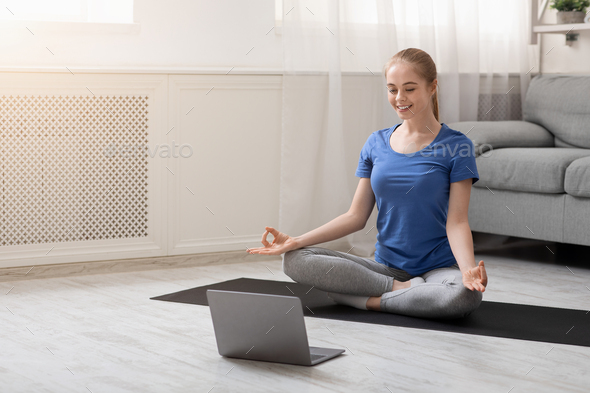 Young spiritual woman practicing yoga at home with laptop - Stock Photo - Images