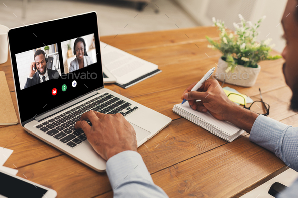 Unrecognizable black man watching business webinar at laptop and writing notes - Stock Photo - Images