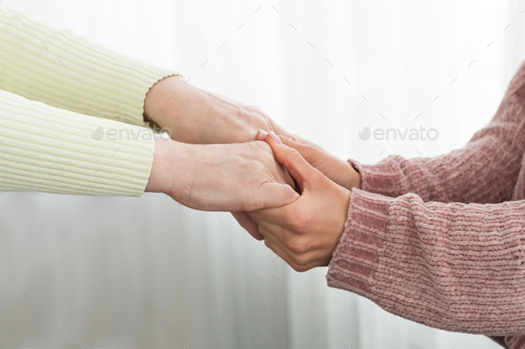 Family support. Senior woman and daughter holding hands - Stock Photo - Images