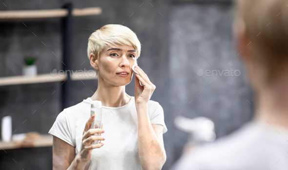 Lady Cleansing Skin With Micellar Water And Cotton Pad Indoors - Stock Photo - Images