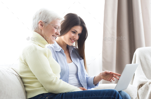 Daughter teaching her elderly mother using laptop - Stock Photo - Images