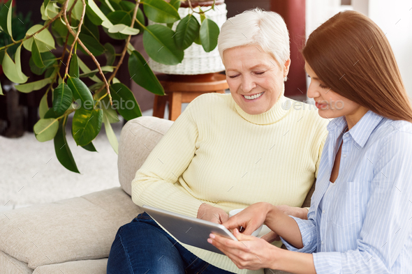 Daughter and mature mother browsing internet on tablet - Stock Photo - Images