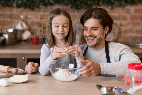 Little girl preparing pastry with dad, adding egg to bowl - Stock Photo - Images