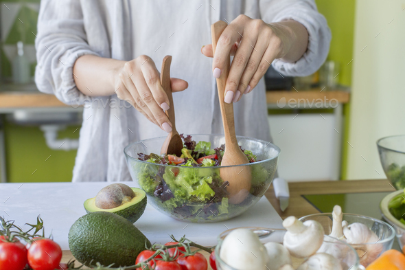 Woman on healthy diet of organic green vegetables making salad - Stock Photo - Images