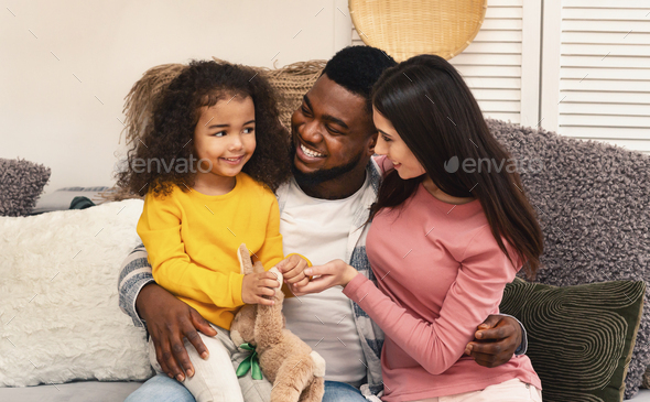 African american dad and european mom are looking at daughter - Stock Photo - Images