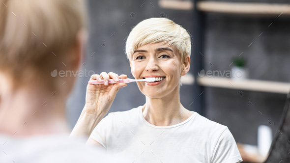Smiling Lady Cleaning Teeth With Toothbrush In Bathroom, Panorama - Stock Photo - Images