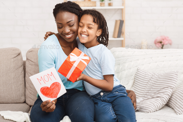Afro kid congratulating her mom at home - Stock Photo - Images