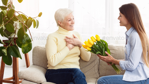 Bouquet of tulips. Woman giving flowers to mother - Stock Photo - Images