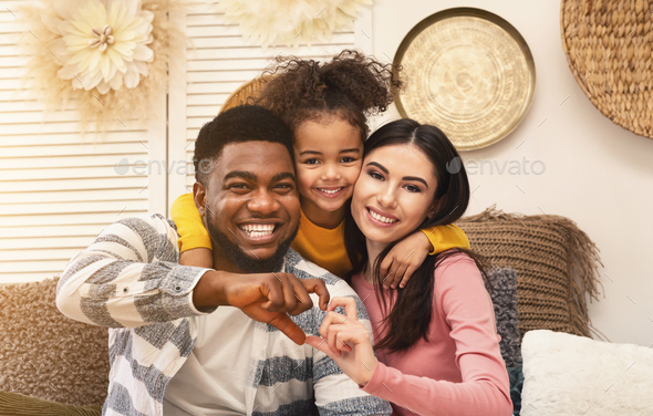 Smiling millennial family on sofa at home - Stock Photo - Images