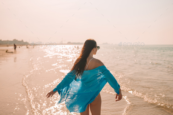 Woman laying on the beach enjoying summer holidays looking at the sea - Stock Photo - Images