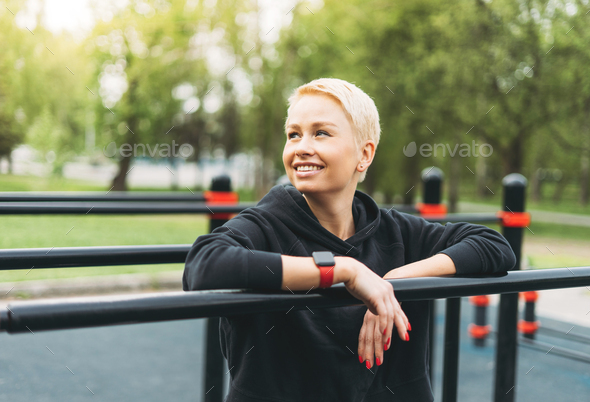 Attractive fit young woman in sport wear rest on street workout area - Stock Photo - Images