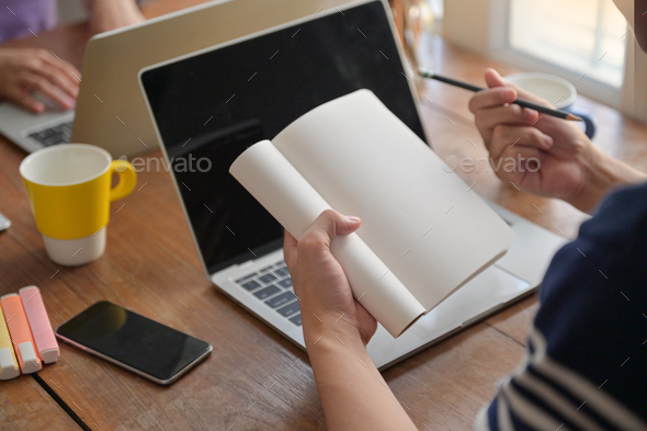 Students are taking notes on their notebook. They are studying online with a laptop at home. - Stock Photo - Images