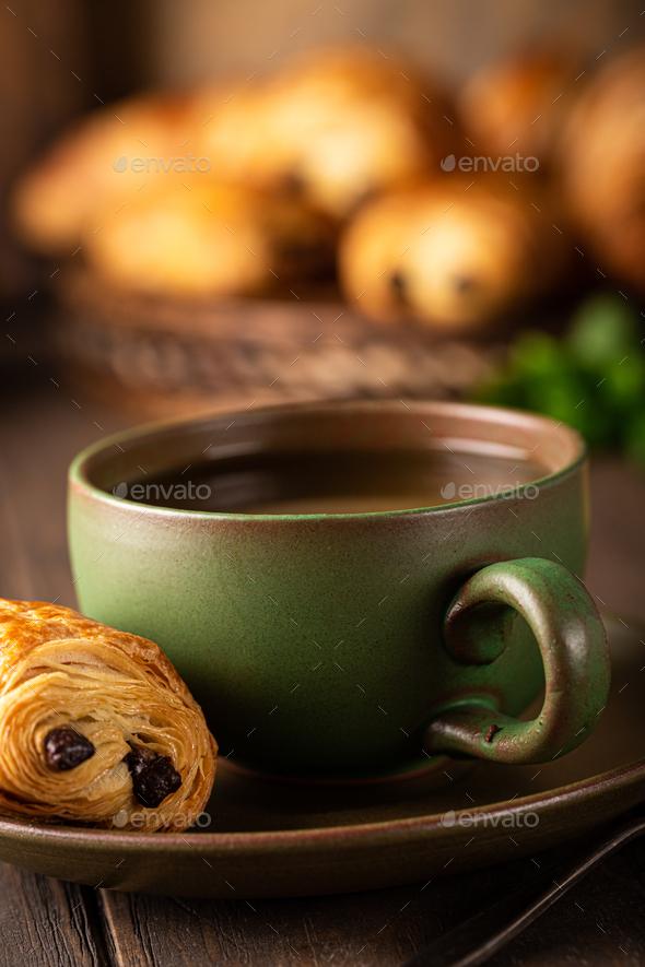 Green cup of tea with mini chocolate bun - Stock Photo - Images