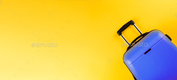 Blue suitcase on a yellow background.Travel concept.Holiday Adventure Trip.Banner. - Stock Photo - Images