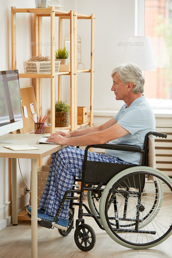 Disabled man working on computer - Stock Photo - Images