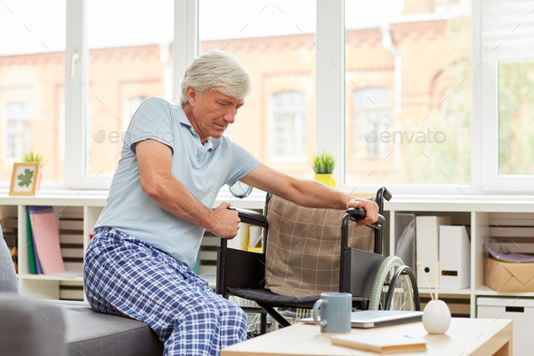 Man is trying to sit in wheelchair - Stock Photo - Images