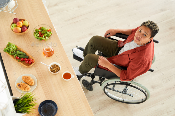 Disabled woman with healthy food on the table - Stock Photo - Images