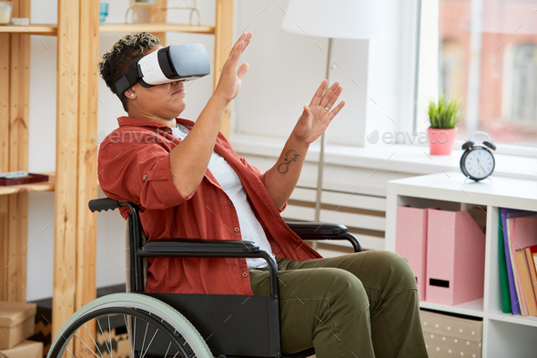 Disabled woman in virtual reality goggles - Stock Photo - Images